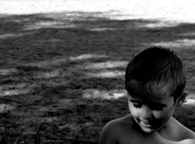 Svartvit pojke på strand