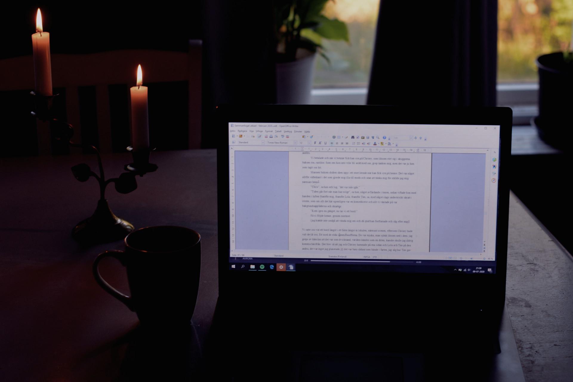 Skriva på en laptop med levande ljus