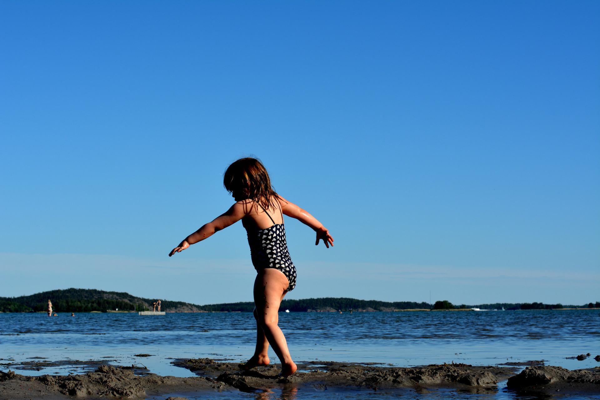 liten flicka promenerar vid havet