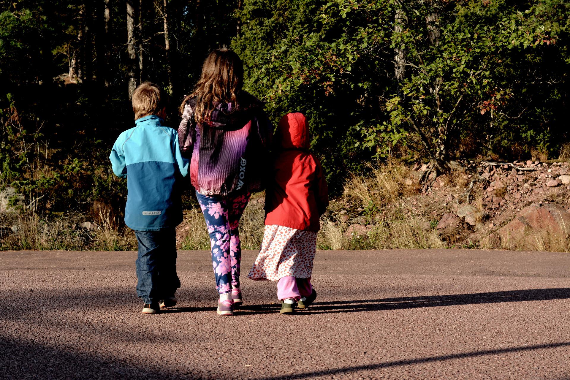 Tre barn tätt i ålder går i solnedgången på asfaltsväg.