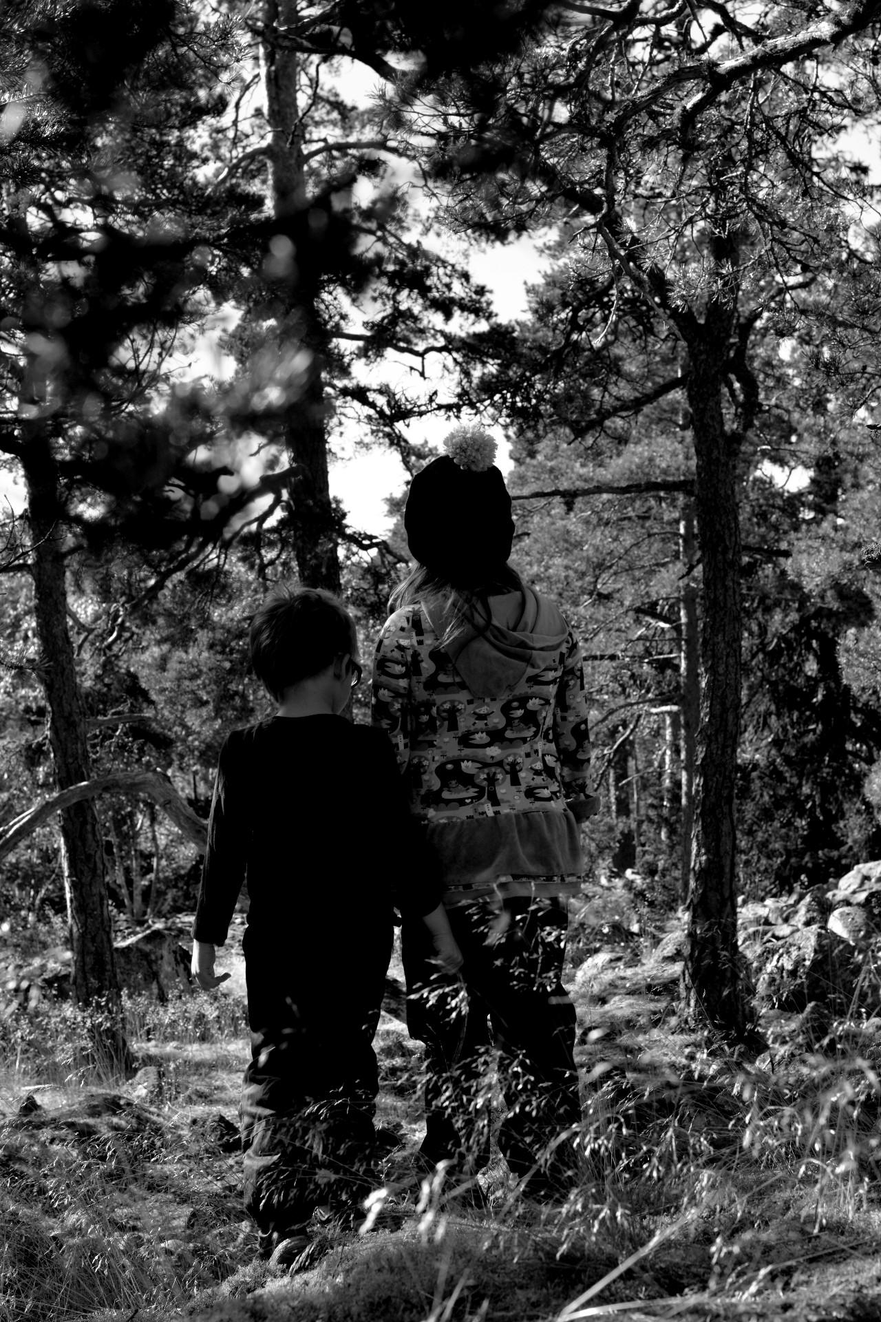 Svartvit bild på storasyster och lillebror i skogen.