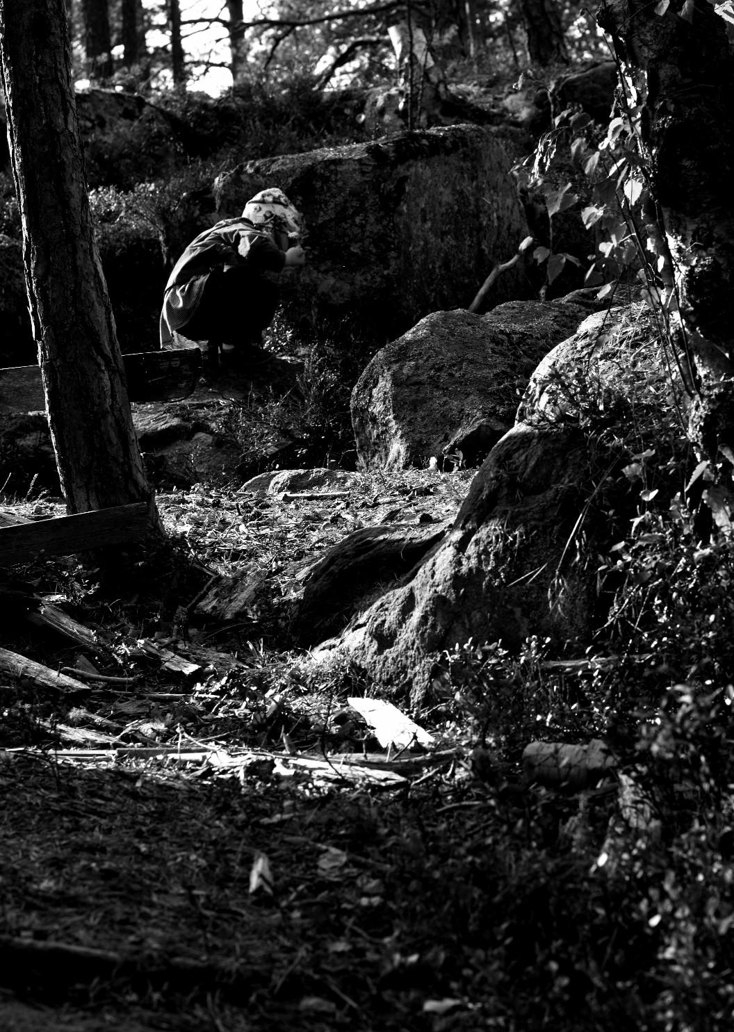 barn på huk i skogen. svartvitt