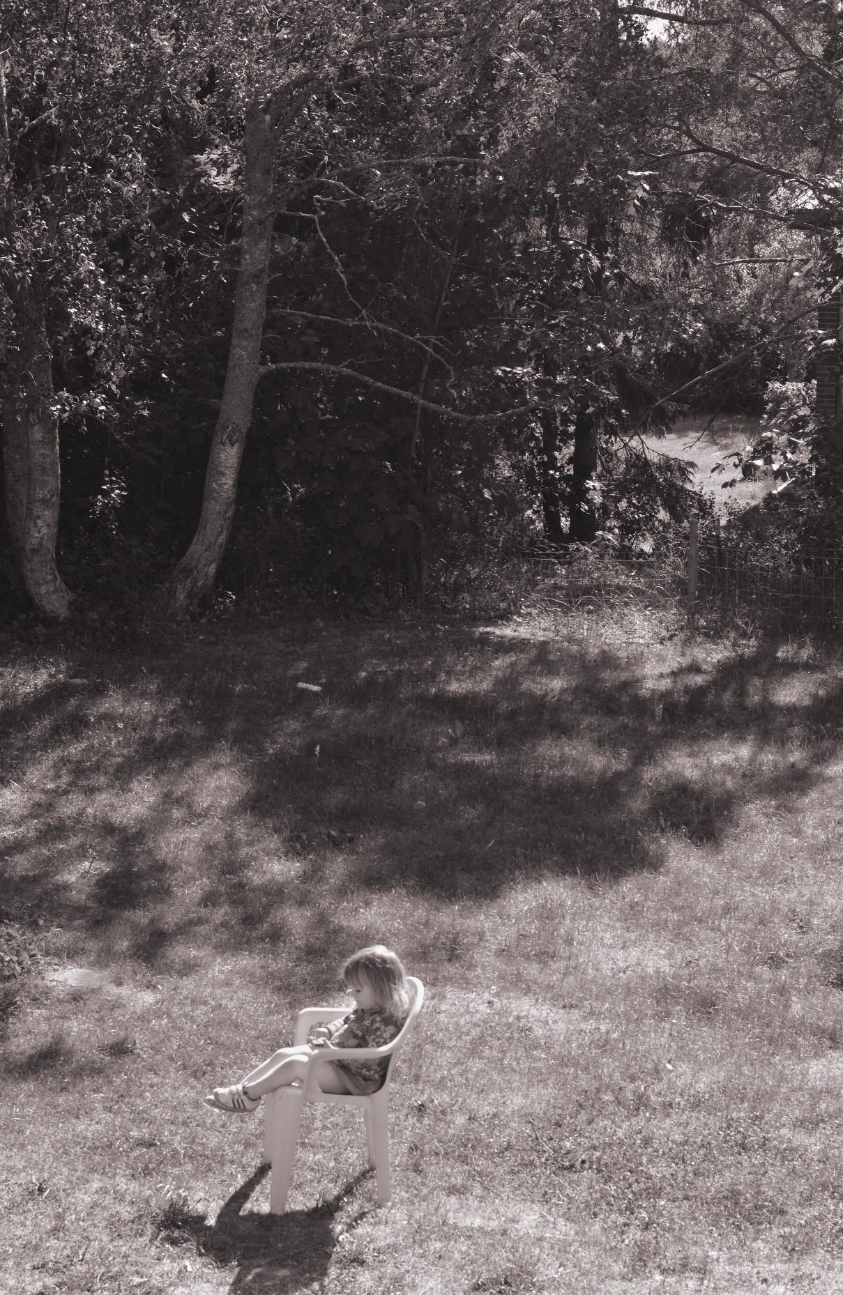 Svartvit rosatonad barn i stol trädgård