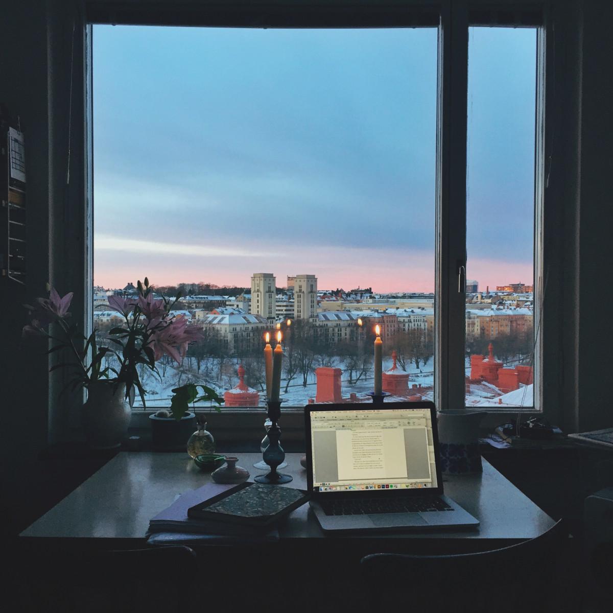Dator med levande ljus vid fönster, skriva.