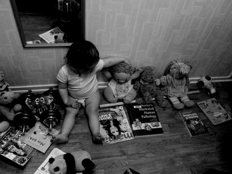 Svartvit bild på barn med gosedjur med böcker