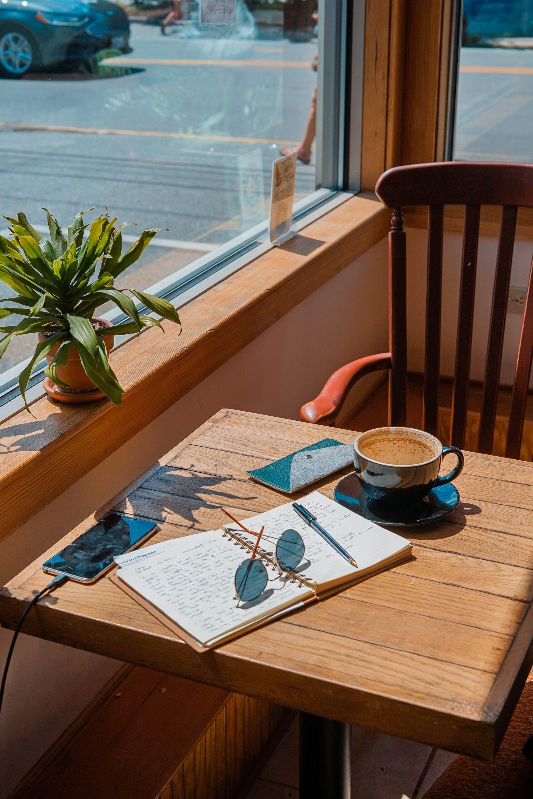 Kaffekopp och skrivblock på café. Jobba med att skriva krönikor.