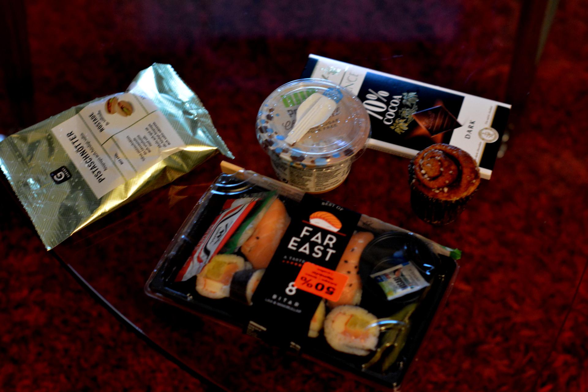 Sushi, pistagenötter, kanelbulle, proteinpudding och mörk choklad på ett bord.