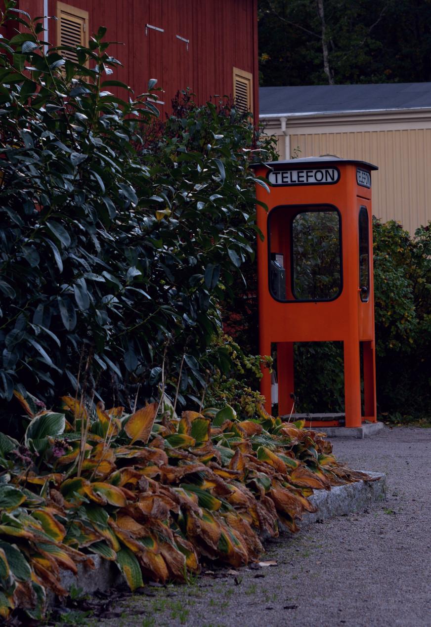 Röd gammal telefonkiosk i Gamla Linköping.