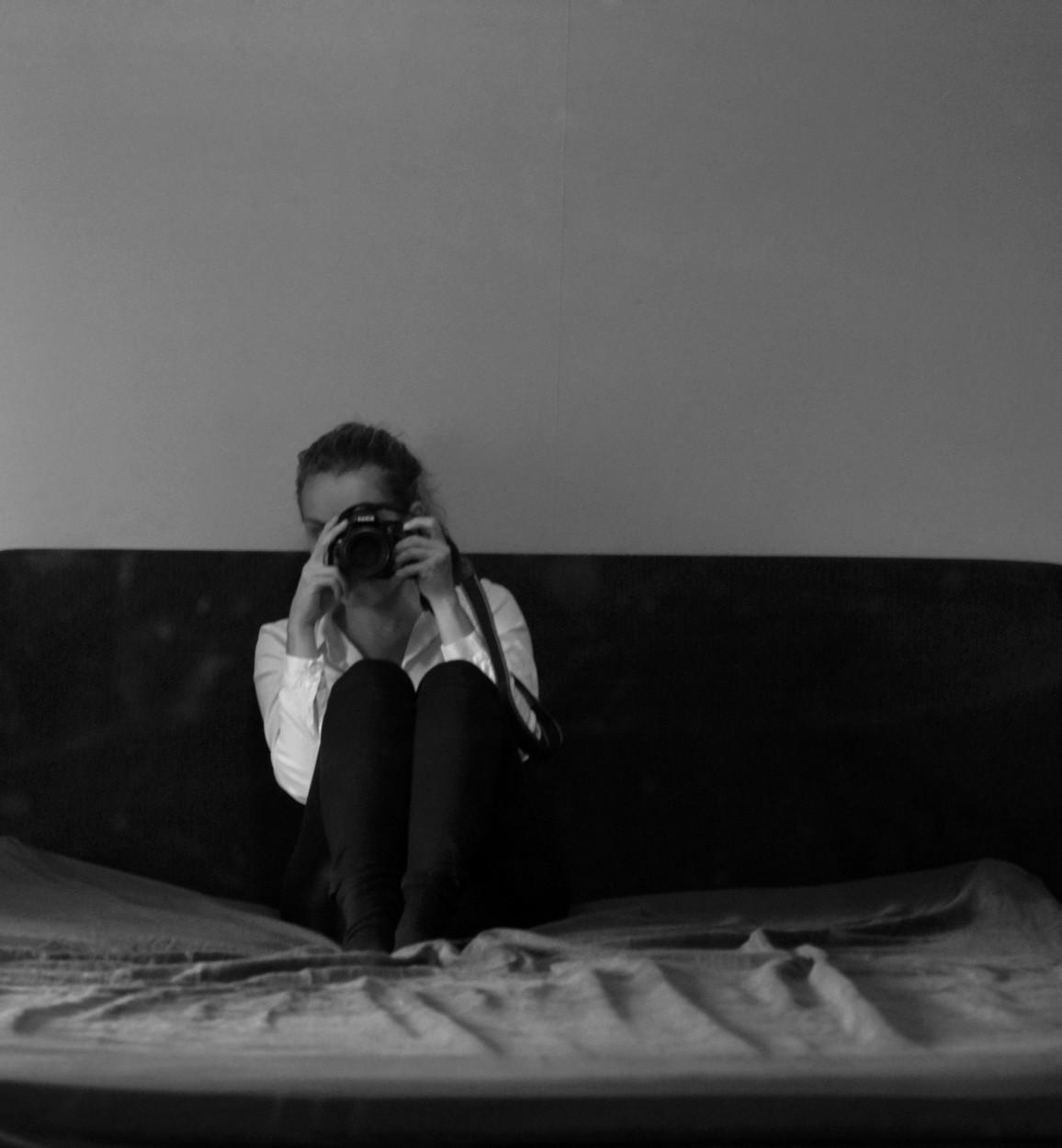 Svartvit bild på skribenten i vit skjorta och jeans med kamera framför ansiktet. Sitter på en säng.