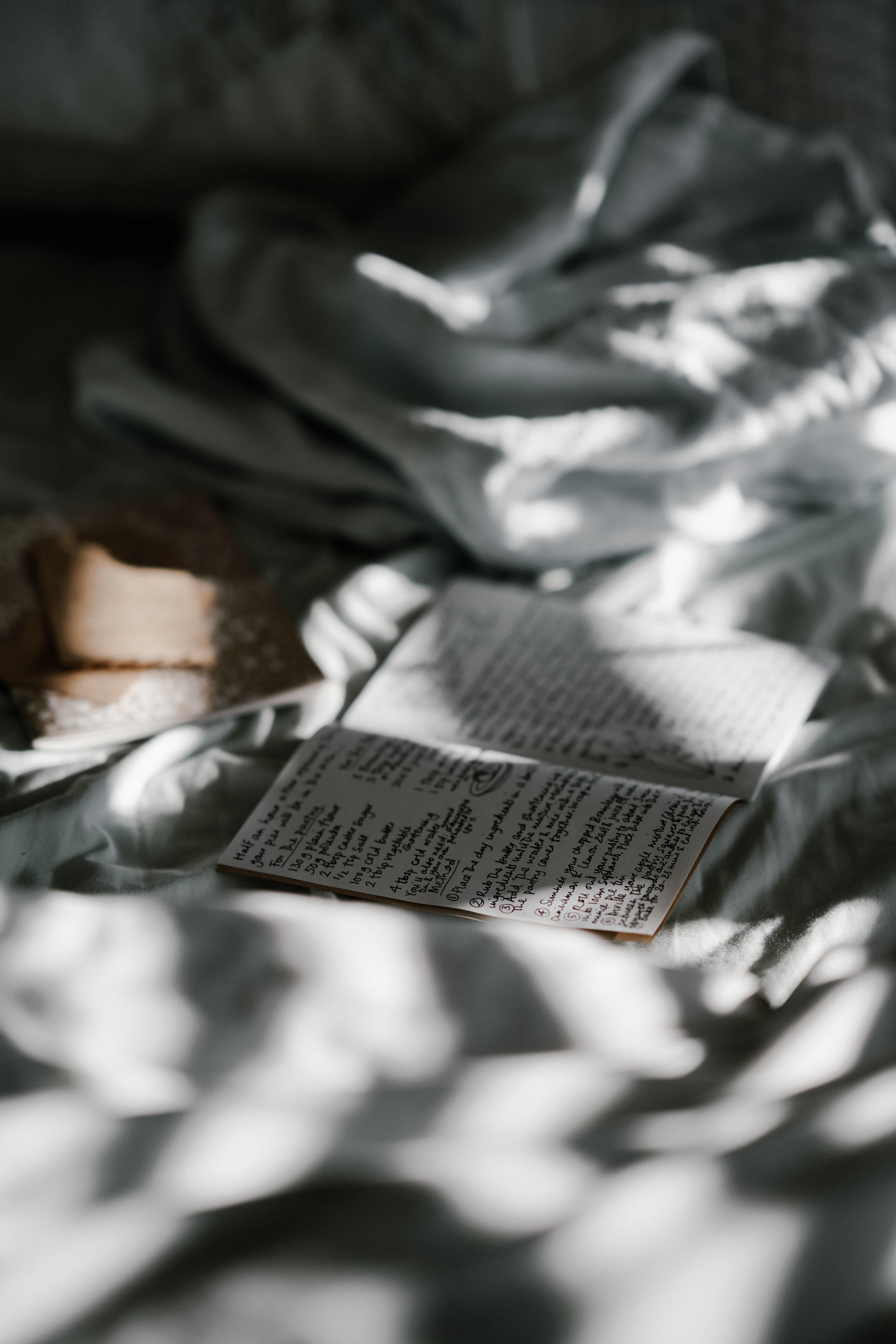 Anteckningsbok på säng i vackert ljus.
