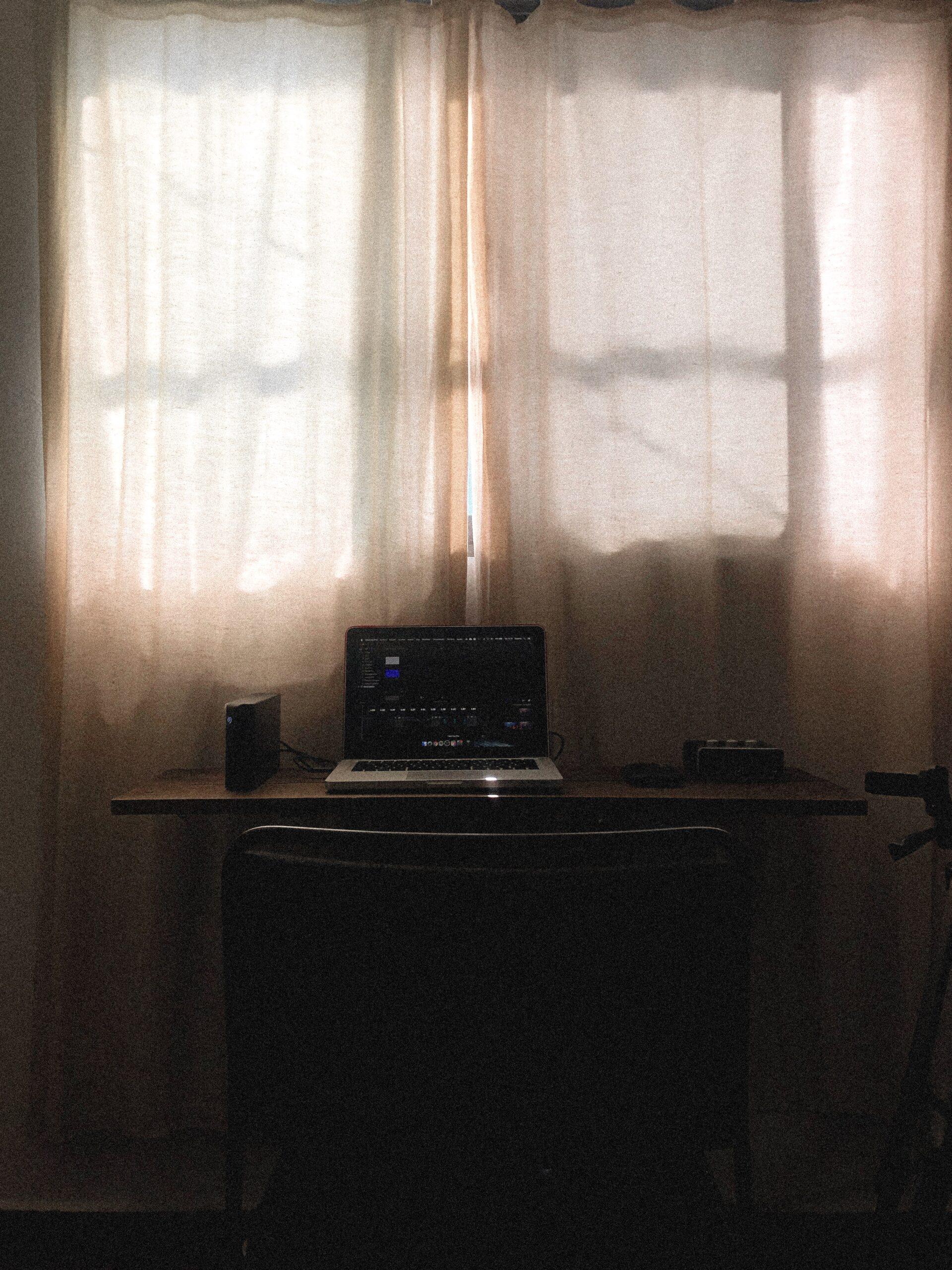 Bild på laptop framför gardiner i motljus.