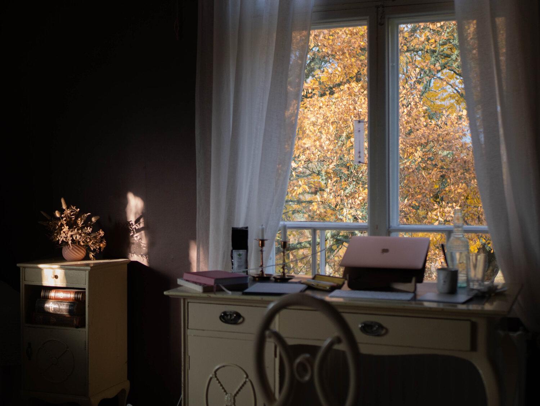 Laptop på skrivbord framför fönster i elegant miljö. Höst utanför.