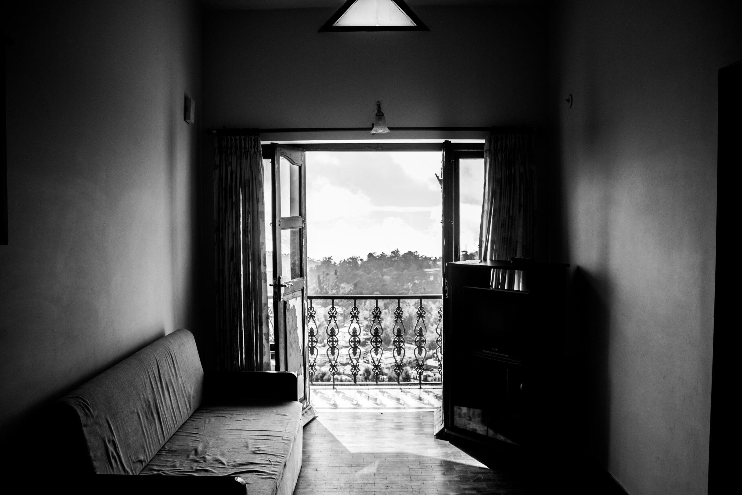 Nedgången öde lägenhet, man ser ut genom öppna balkongdörrar på vacker vy. Svartvit.