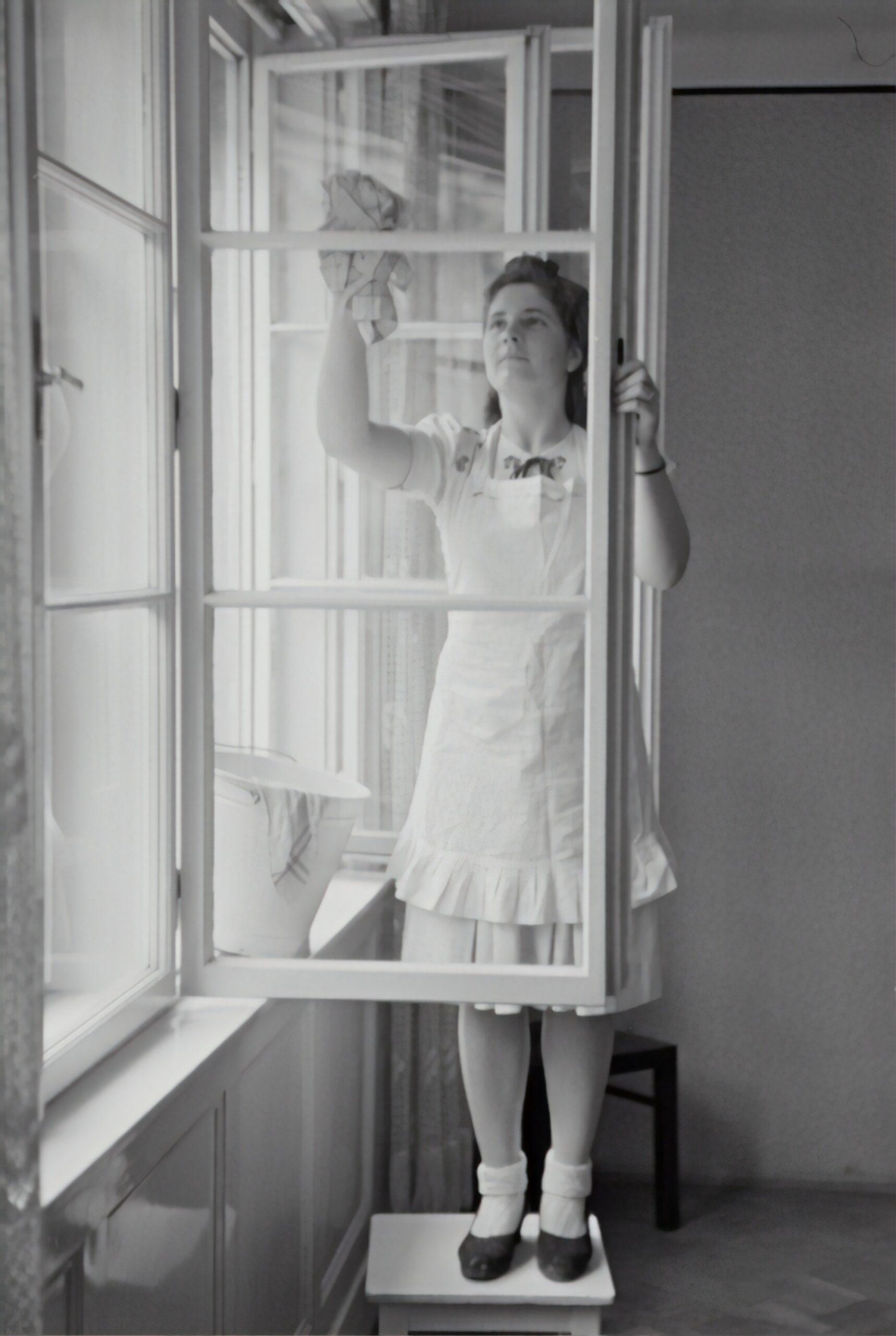 Svartvit gammal bild på kvinna som putsar fönster.