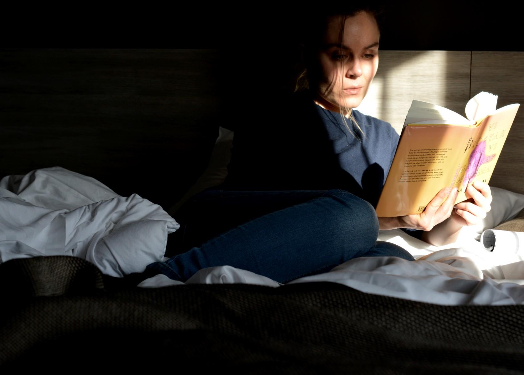 Kvinna i solljus läser Vi röstar om vi saknar mamma av Nina Pascoal.