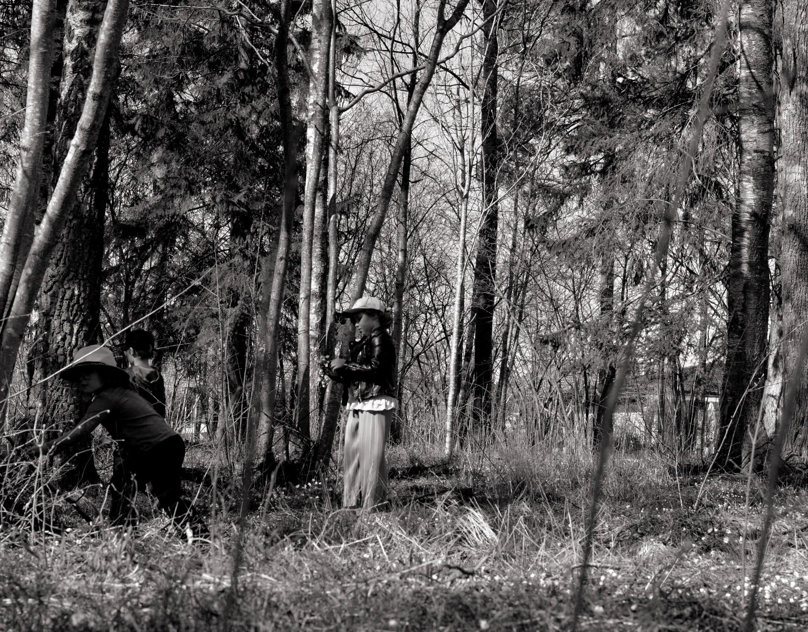 Svartvit bild på barn som leker i skog på våren.