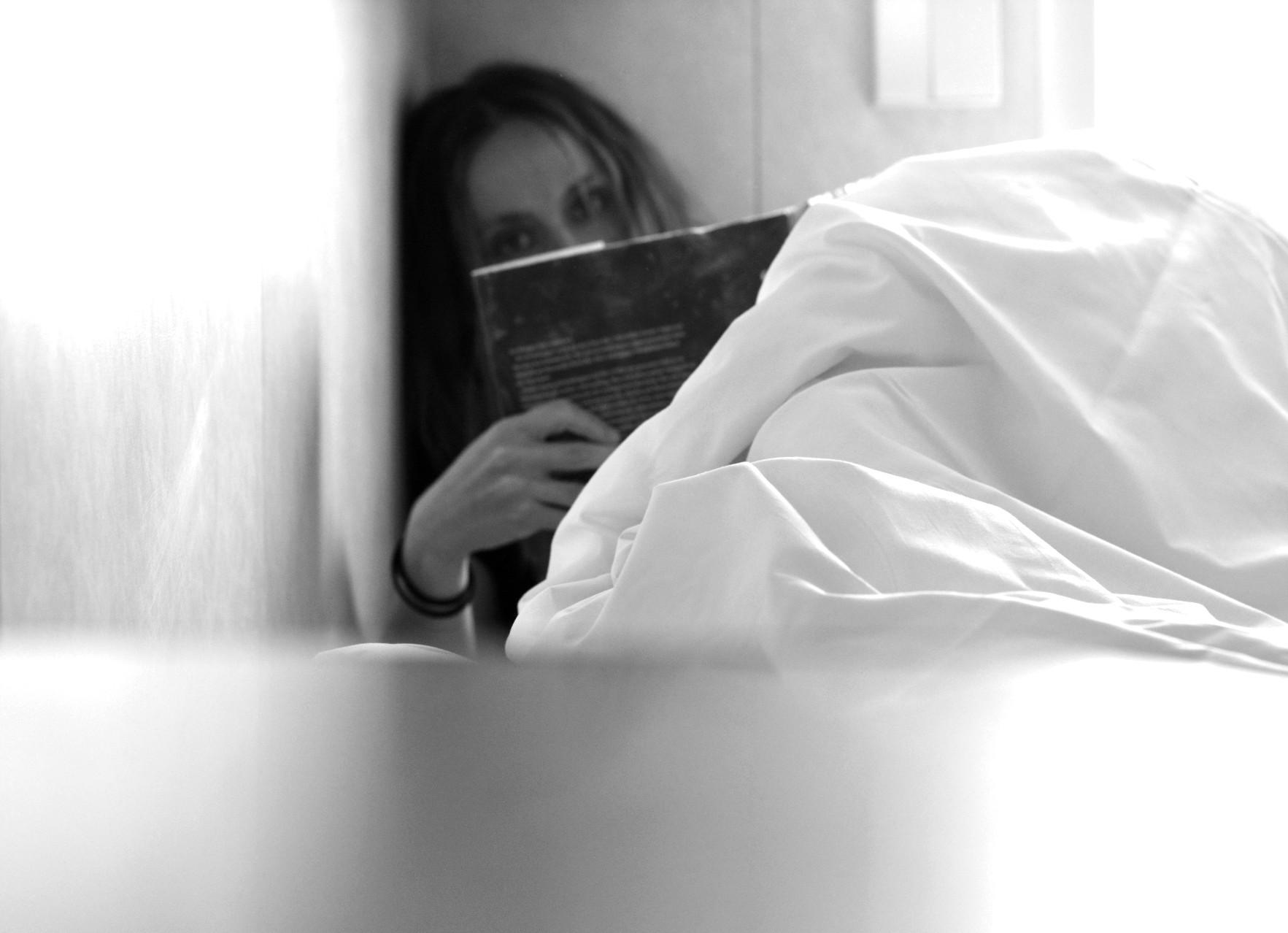 Svartvit bild på kvinna som läser bok i hytten på en färja.