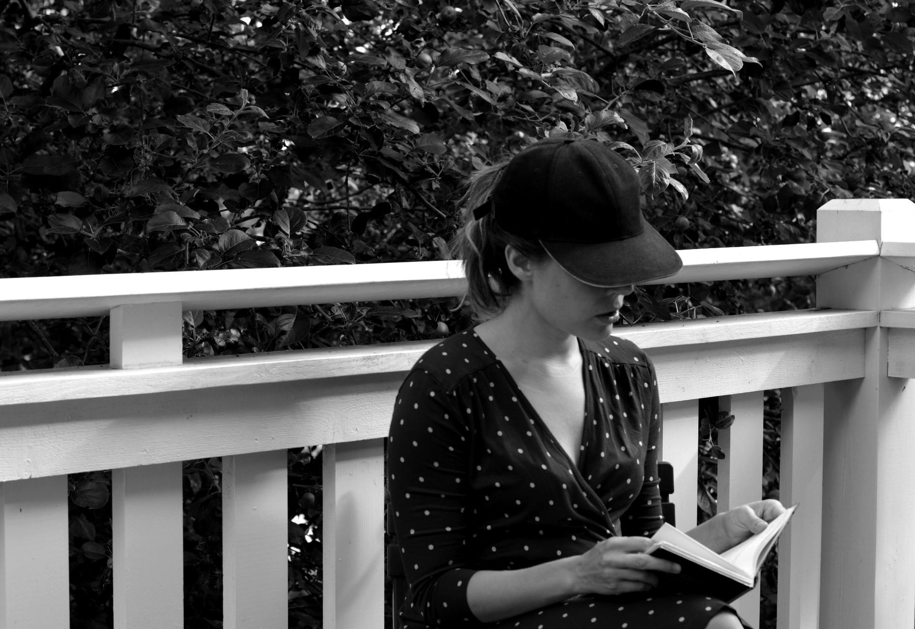 Ulrika Nettelblad läser en bok på balkong. Svartvit bild.