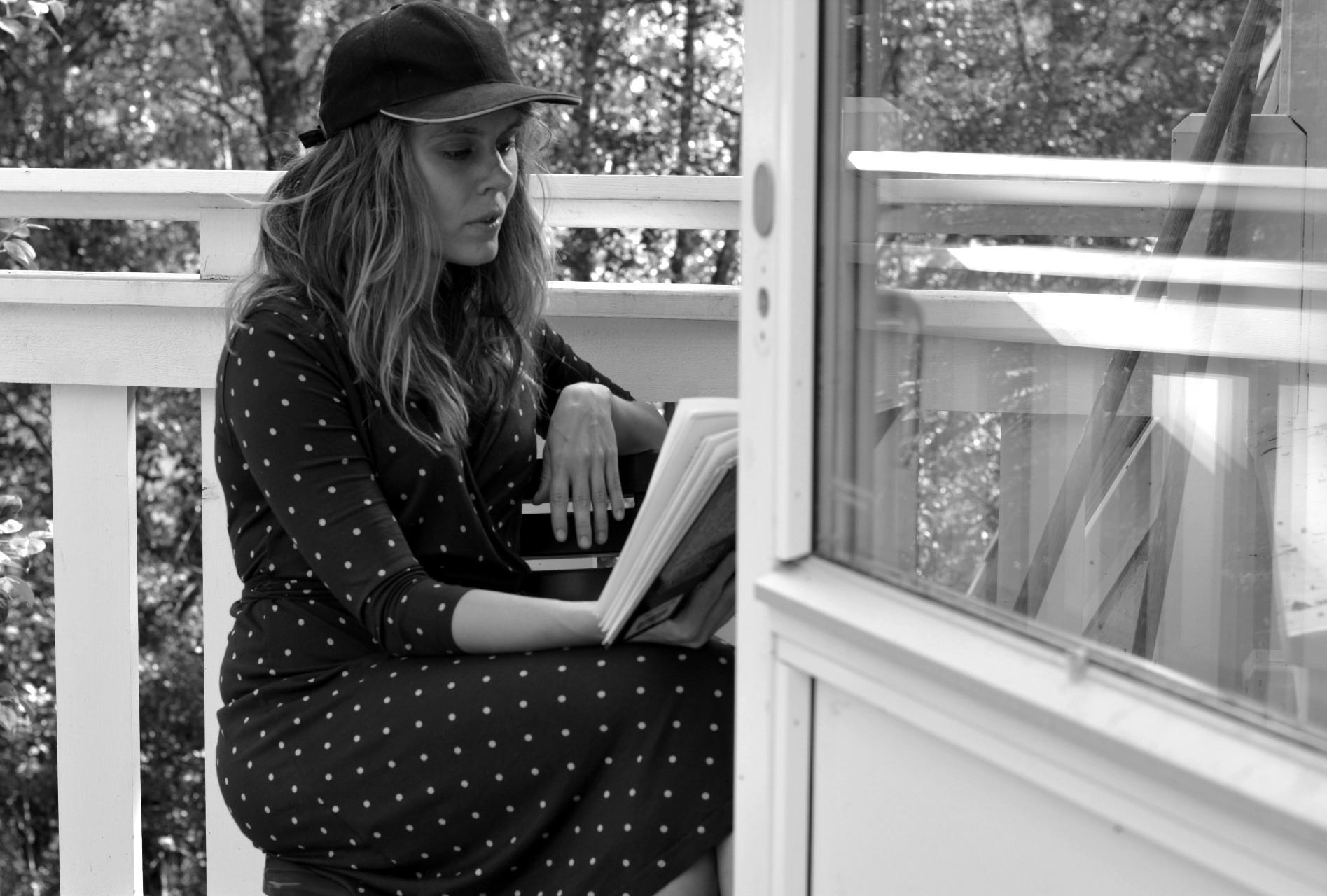 Svartvit bild på Ulrika Nettelblad som läser bok på en balkong